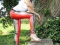 rubber redhead wearing skin tight colored latex leggings outside